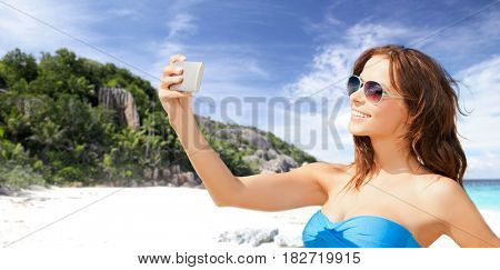 technology, summer holidays, travel and people concept - happy young woman in bikini swimsuit and sunglasses taking selfie with smatphone over beach and palm trees background