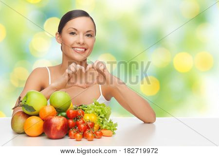 diet, healthy eating, food and people concept - happy woman with lot of fruits and vegetables showing heart over green summer lights background