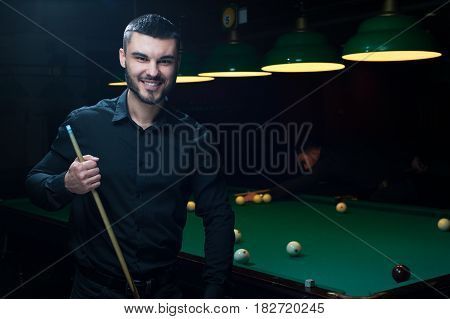 Handsome young man wearing black casual cloth posing with billiard cue. Green snooker table with balls on background