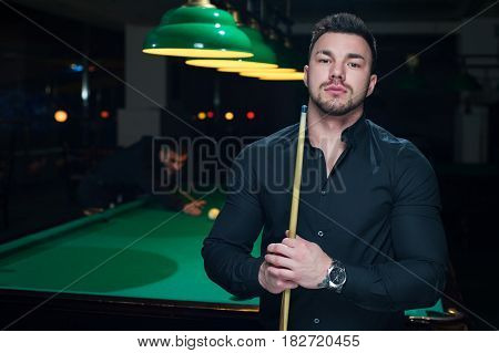 Two male adults playing snooker game in club. Young handsome man standing with billiard cue. Green pool table with balls background