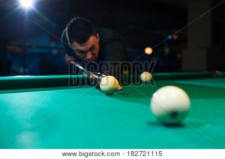 Cropped shot of male adult playing billiard game. Young caucasian man aiming the ball with cue. Green snooker table.