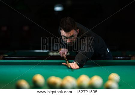 Focused young man wearing casual cloth aiming to take snooker shot. Male adult playing billiard game in club.