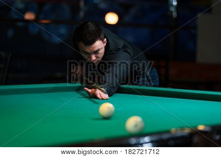 Young focused adult playing billiard game. Concentrated man aiming to take the snooker shot.