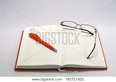 a daily planner with glasses and pen