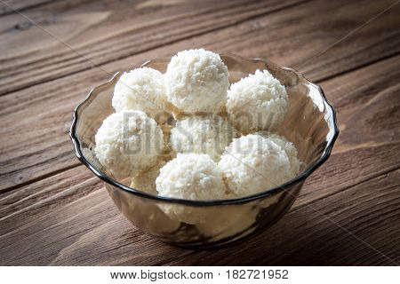 Sweet coconut candyes in glass bowl on wooden background