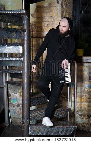 A bearded man with a mini piano. A bearded guy in fake sneakers and a piano. The guy on the stairs