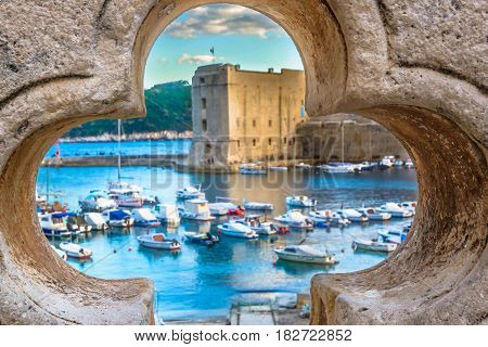 Scenic view through stone hole at coastal town Dubrovnik, famous touristic destination in Europe, Croatia.