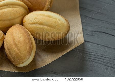 Cookies with boiled condenced milk on cooking paper with wooden background, close-up
