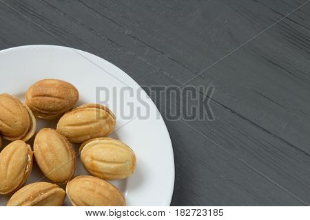 Homemade cookies with condenced milk on a white plate in a corner, wooden background