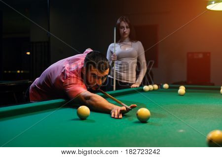 Romantic couple having fun playing billiard game in club. Young man aiming to take a snooker shot while brunette girl standing next to.