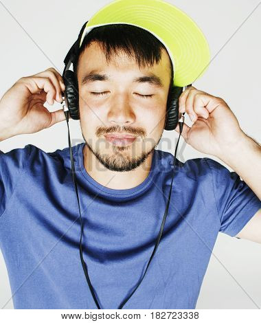 young asian man in hat and headphones listening music on white background close up