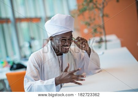 Sudanese business man in traditional outfit using mobile phone in office.