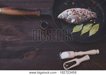 Fresh crucian in a frying pan with pepper and salt in a black frying pan top view vintage toning