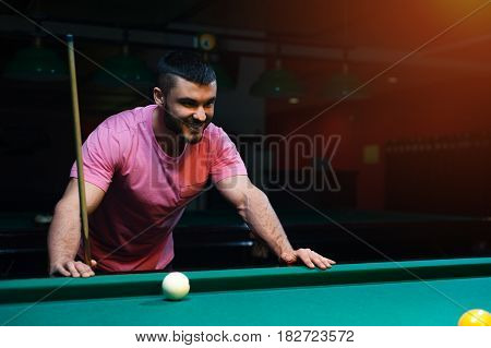 Happy smiling young man playing billiard game in club. Male adult wearing casual wear with snooker cue.
