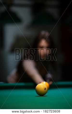 Attractive brunette girl playing billiard game. Young caucasian woman with cue on the background of green snooker table. Defocused background