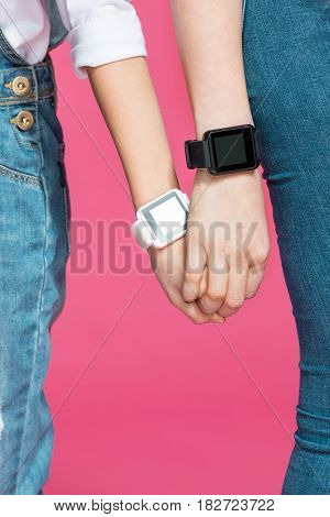 Close-up Partial View Of Mother And Daughter Holding Hands With Smartwatches