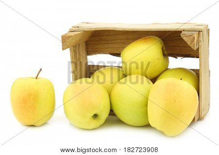fresh yellow apples and a cut one in a wooden crate  on a white background