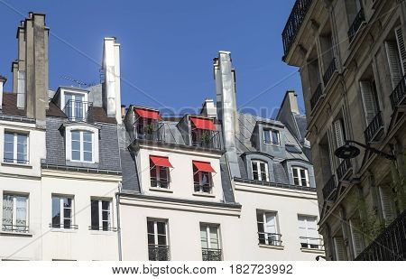 Red sun awnings on the windows of the attic. Paris France.