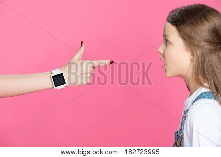 Side View Of Shocked Little Girl Looking At Woman With Smartwatch Pointing With Finger