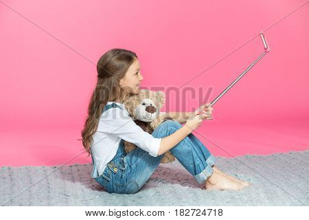 Side View Of Smiling Little Girl Sitting With Teddy Bear And Taking Selfie