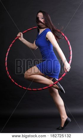 Beautiful woman in a sport wear. Dance hoop gym exercises black background