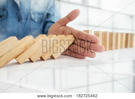 Problem Solving Close up view on hand of business woman stopping falling blocks on table for concept about taking responsibility.