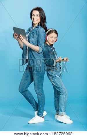 Happy Mother And Daughter In Headphones Using Digital Tablet And Smartphone In Studio On Blue