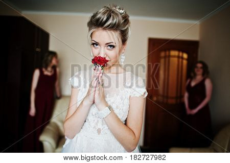 Blonde Bride With Buttonhole On Hands Against Bridesmaids Wear On Red Dress At Room On Morning Weddi