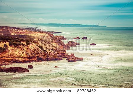 Rugged Ocean Coastline With Eroded Rocks And Breaking Waves.