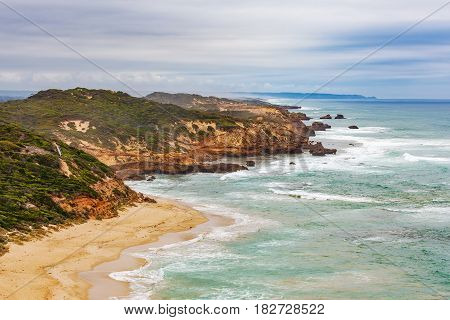 Rugged Coastline, Coastal Vegetation, Breaking Waves, And Eroded Rocks.