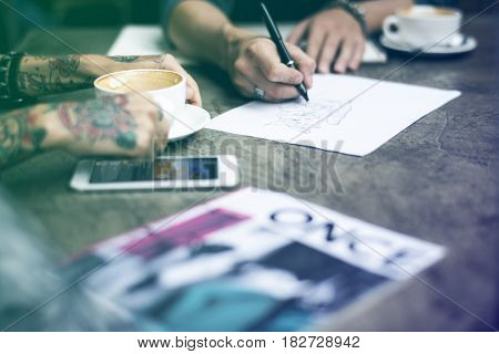 People drawing and sharing ideas at coffee shop