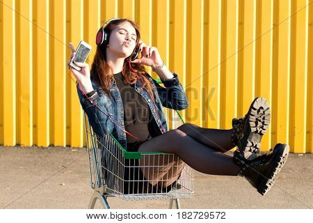 Cheerful Stylish Young Girl In Jeans Jacket, Shoes And Skirt, Listening To Music In Headphones With