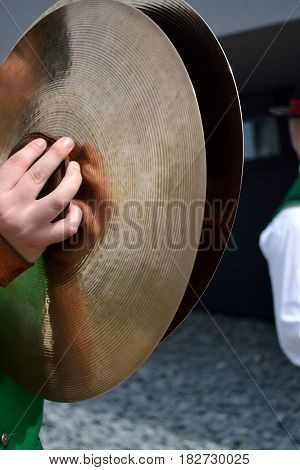 Musician in costume with the instrument cymbals - close-up