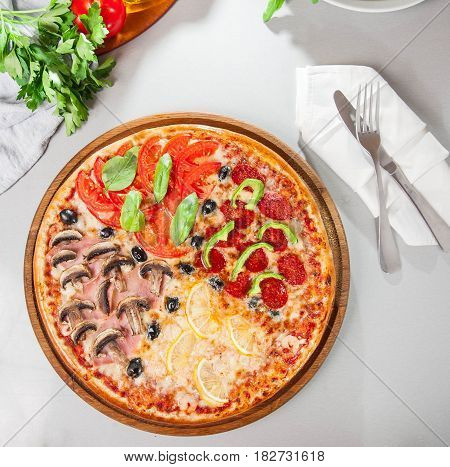 Top View Fresh Italian Four Seasons Pizza (pizza Quattro Stagioni) On The Wooden Board On The Kitche