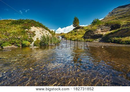 Mountain stream with clear and transparent water among alpine meadows.Trek near Matterhorn mount. View of the mountain and valley of a mountain river. Beautiful alpine landscape with a mountain path, Swiss Alps, Europe
