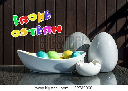 Set of colorful shiny Easter eggs and grey and white colored ceramic with text happy easter in german