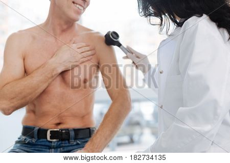 Detailed examination of skin problems . Young optimistic friendly dermatologist working in the hospital and having conversation with patient while examining man torso with dermatoscope