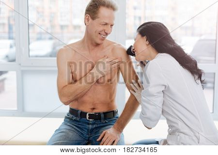 Looking for cancerous formation. Young skilled capable dermatologist working in the hospital and listening to the patient complaint while examining man torso and using dermatoscope
