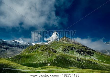 Summit of the Matterhorn mount and green alpine meadows. View of the Alpine mountains at the sunrise. Trek near Matterhorn mount.