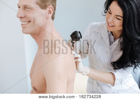 Checkup of injured birthmarks. Smiling cheerful qualified specialist working in the clinic and enjoying working hours while examining man back and using special equipment