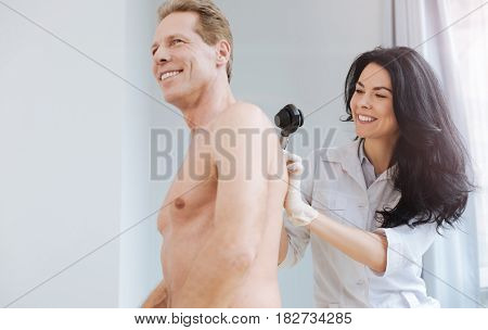 Preventing risk of cancerous moles. Experienced smiling cheerful doctor working in the clinic and enjoying appointment while examining man back and using dermatoscope