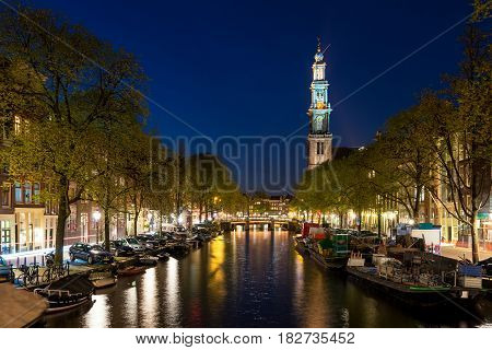 Amsterdam Westerkerk church tower at canal in the city of Amsterdam Netherlands.