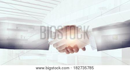 Business handshake as symbol of deal . Mixed media
