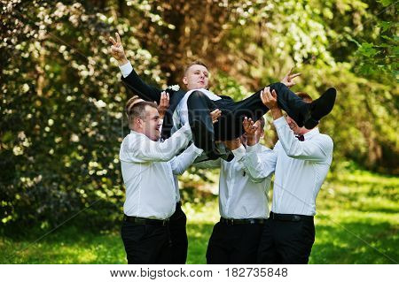 Fashionable Groom With Four Best Mans At Bow Ties Outdoor. Friends Tossed Into The Air At Theyu Hand