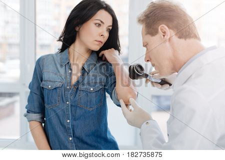 Exploring allergy reaction. Concentrated smart aged dermatologist working in the hospital and having appointment with patient while taking dermatoscope for skin examination poster