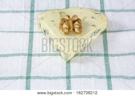 Palatable cheese roquefort with one walnut is on the towel