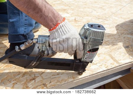 Construction worker using nail gun to nail Oriented Strand Board osb sheeting on roof of a new home