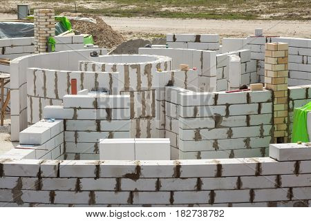 Constraction workers building a roundhouse with aerated autoclaved concrete blocks