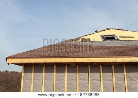 Roofing Construction and Building New Brick House with Skylights Attic Dormers and Eaves. Repair Asphalt Shingles or Bitumen Tiles on the Rooftop Outdoor.