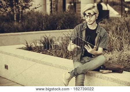 Male fashion technology student concept. Guy with tablet and bag full of notebooks wearing jeans outfit sitting on white ledge next to flowers sepia